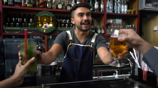 Friendly bar tender serving drinks to an unrecognisable couple sitting at the bar counter Friendly bar tender serving drinks smiling very happy to an unrecognisable couple sitting at the bar counter wait staff stock videos & royalty-free footage
