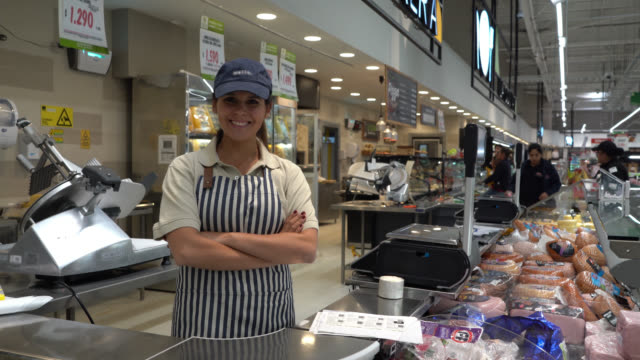 Friendly beautiful sales woman at a delicatessen standing behind counter smiling at camera with arms crossed Friendly beautiful sales woman at a delicatessen standing behind counter smiling at camera with arms crossed - Retail concepts saleswoman stock videos & royalty-free footage