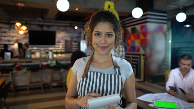 przyjazna piękna kelnerka w biurze coworkingowym trzymająca notatnik zwrócony w stronę kamery uśmiechniętej - kelner filmów i materiałów b-roll