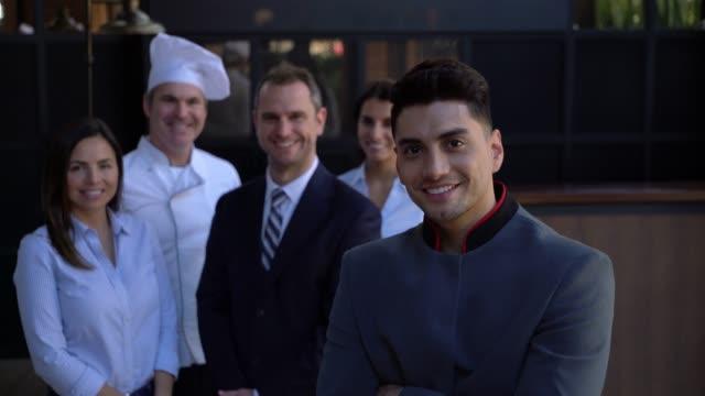 腕を組んでカメラと笑顔の背景で、ホテルのチームに立っての残りの部分に直面してフレンドリーなベルボーイ - 外食産業関係の職業点の映像素材/bロール