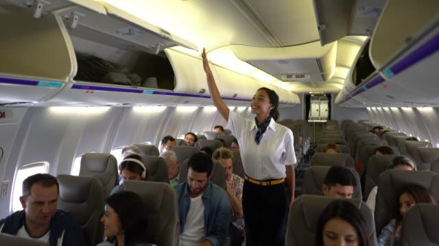 친절 한 검은 항공 스튜 어디 스 상업 비행기에서 오버 헤드 구획을 닫기 - airplane seat 스톡 비디오 및 b-롤 화면