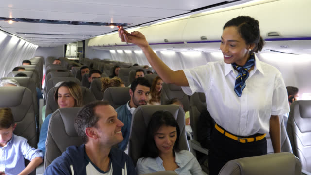 Friendly black stewardess turning off the button while talking to female passenger to help her with something