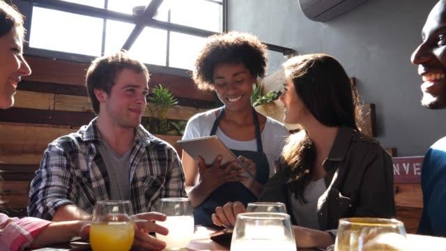 friendly black waitress taking an order from a group of diverse friends using a computer tablet - kelner filmów i materiałów b-roll