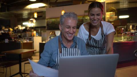 vídeos y material grabado en eventos de stock de dueño de negocio amistoso sobre algunos documentos y la información del restaurante con mujer gerente ambos feliz - small business