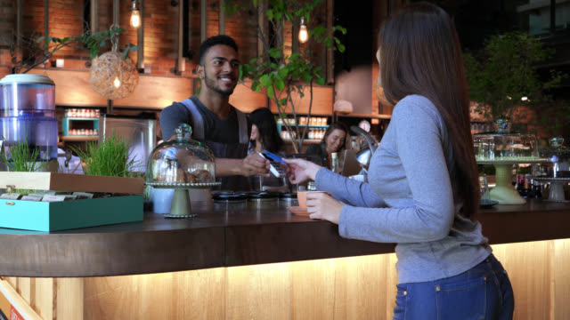 Friendly business owner serving coffee to female customer who pays her order with credit card