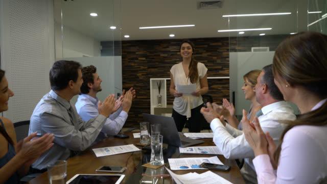 vídeos de stock, filmes e b-roll de mulher de negócios amigável agradecendo a equipe dela enquanto eles aplaudem-la depois de uma apresentação - agradecimento