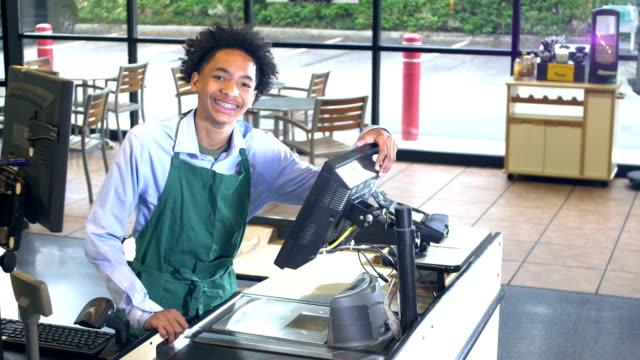 vídeos de stock e filmes b-roll de friendly cashier at supermarket checkout - afro americano