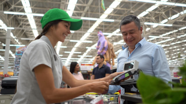 friendly cashier receiving credit card from customer to process a purchase at the supermarket - icona supermercato video stock e b–roll