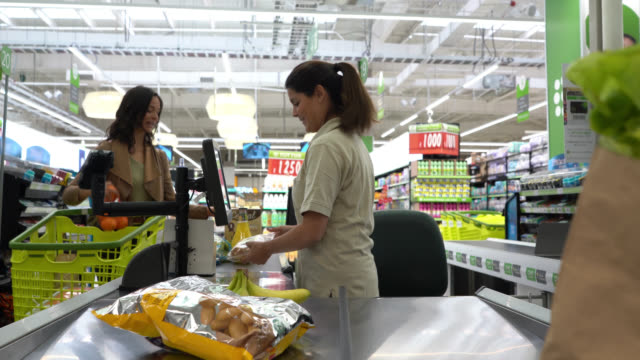 Friendly cashier registering products with bar code reader at a supermarket checkout to female customer Friendly cashier registering products with bar code reader at a supermarket checkout to female customer both smiling register stock videos & royalty-free footage
