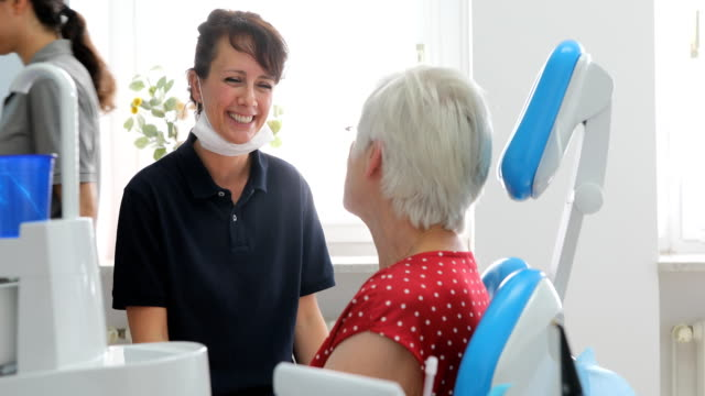 vídeos y material grabado en eventos de stock de dentista amigable hablando con paciente femenina en la clínica - ortodoncista