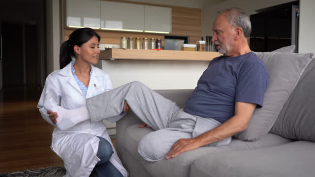Friendly doctor checking a disabled senior diabetic patient at his home Friendly doctor checking a disabled senior diabetic patient at his home – Lifestyles amputee stock videos & royalty-free footage