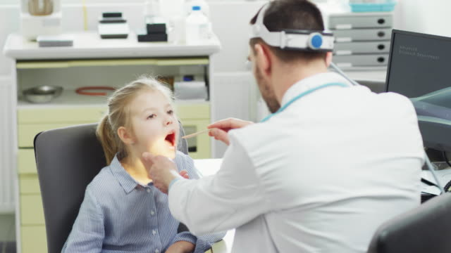 少女の喉の硬化インフルエンザをフレンドリーな医者をチェックします。現代医療、優しい小児科医、明るいオフィス。 - 聴診器点の映像素材/bロール
