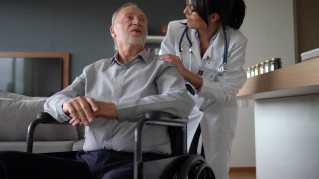 ev çağrı dostu doktor tekerlekli sandalye üzerinde engelli bir kıdemli hasta kontrol - ziyaret stok videoları ve detay görüntü çekimi