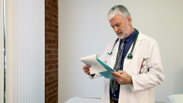 Friendly Doctor A friendly gray haired doctor reviews documents on a clip board.  Locked down. test results stock videos & royalty-free footage
