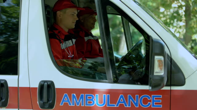 Friendly doctors in ambulance looking at camera, professional emergency service Friendly doctors in ambulance looking at camera, professional emergency service rescue worker stock videos & royalty-free footage