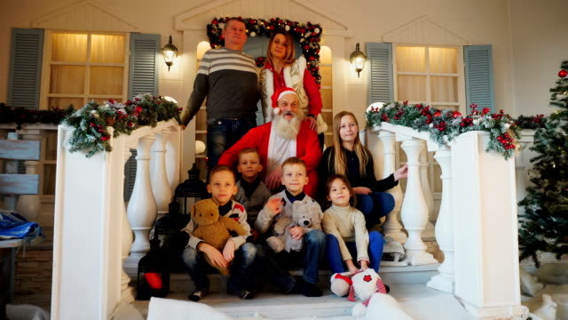 Friendly family and Santa Claus posing for camera on porch of house decorated for New Year video