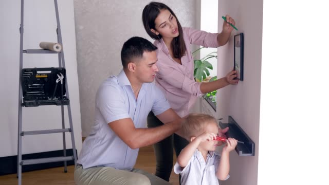 friendly family with small child boy doing redecorating and screwing shelf and picture to wall