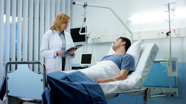 Friendly Female Doctor Visits Happy Recovering Man who is Lying in Bed, She Asks Him Questions and Fills Medical Chart. Friendly Doctor and Sick Man in a Clean Hospital Ward. Friendly Female Doctor Visits Happy Recovering Man who is Lying in Bed, She Asks Him Questions and Fills Medical Chart. Friendly Doctor and Sick Man in a Clean Hospital Ward. Shot on RED EPIC-W 8K Helium Cinema Camera. military private stock videos & royalty-free footage