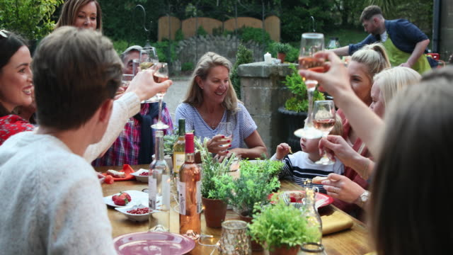 A Friendly Get Together A social gathering of a large group of mixed age friends. The main focus is on one table, guests are sitting and have a celebratory toast while talking and laughing. A woman in the forefront feeds a man garlic bread. party social event stock videos & royalty-free footage