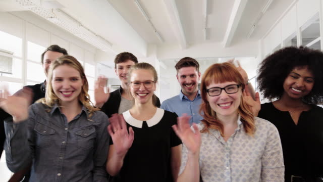 Friendly group of employees rejoicing in office