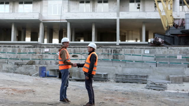 Friendly handshake of two builders at a construction site. Discussion of the construction schedule of a high-rise monolithic house. - vídeo