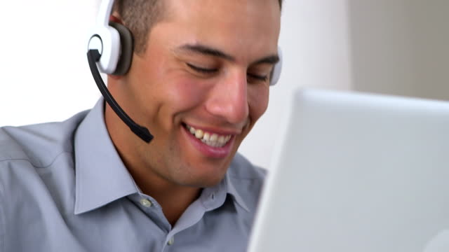 Friendly Hispanic telemarketer working at computer video