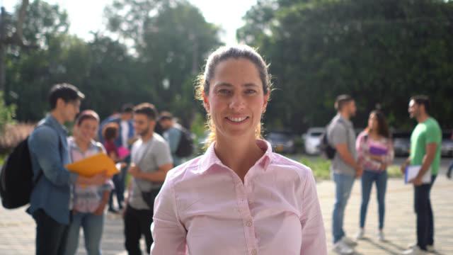 friendly latin american female teacher facing camera very confident at the university campus - instruktor filmów i materiałów b-roll