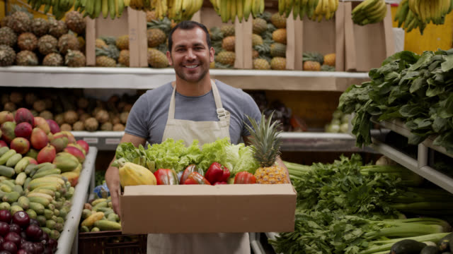 Friendly man preparing a delivery for customer in a cardboard box full of fresh fruits and vegetables looking at camera smiling Friendly man preparing a delivery for customer in a cardboard box full of fresh fruits and vegetables looking at camera smiling - Responsible business homegrown produce stock videos & royalty-free footage