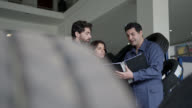 istock Friendly mechanic talking to couple customer about the work to do in their car and handshaking after doing an agreement 1199982707