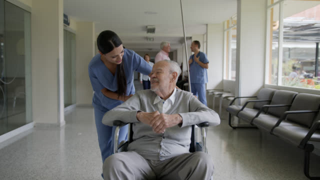 Friendly nurse talking to senior patient while pushing him on wheelchair at the hospital's corridor Friendly nurse talking to senior patient while pushing him on wheelchair at the hospital's corridor - Incidental people at background pushing wheelchair stock videos & royalty-free footage
