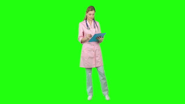 Friendly Nurse Beautiful young nurse standing on green screen background, writing something then looking at camera and smiling full length stock videos & royalty-free footage