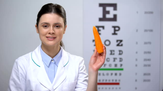 Friendly oculist recommending carrot for maintaining good vision, healthy food Friendly oculist recommending carrot for maintaining good vision, healthy food eye chart stock videos & royalty-free footage