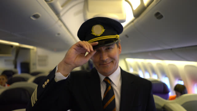 Friendly pilot standing at the passenger cabin looking and waving to camera very happy