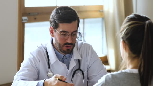 friendly professional male doctor consulting woman patient at medical consultation - пациент стоковые видео и кадры b-roll