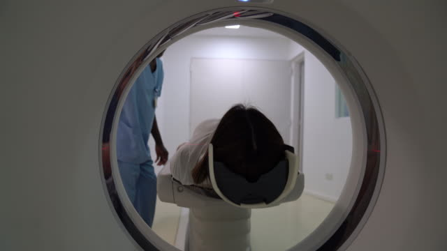 vídeos de stock e filmes b-roll de friendly radiologist getting a female patient ready for a brain scan - tumor cerebral