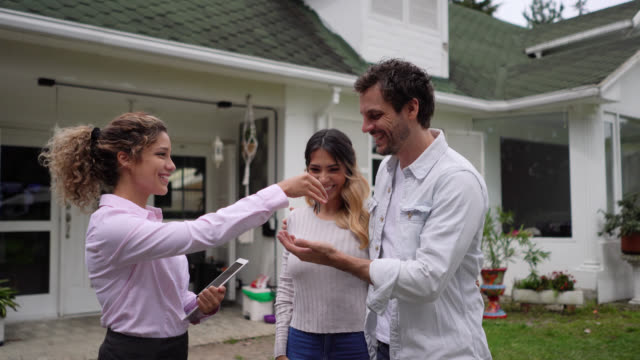 Friendly realtor handing the keys to their new home to couple while they hug very excited