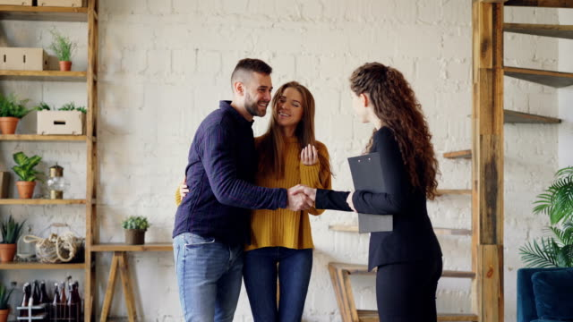 Friendly realtor is giving keys to young couple buyers of new house, happy spouses are hugging and kissing, man is shaking hands with broker making deal.