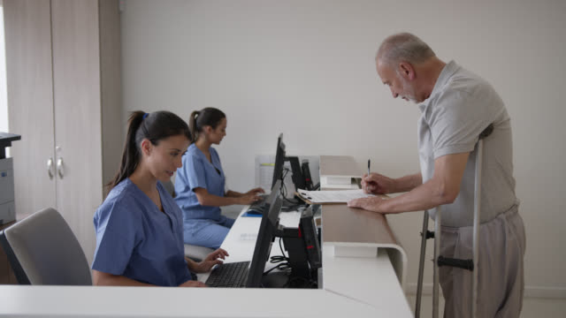 Friendly receptionist helping disabled man fill in a form at the hospital before his appointment Friendly receptionist helping disabled man fill in a form at the hospital before his appointment - healthcare concepts crutch stock videos & royalty-free footage