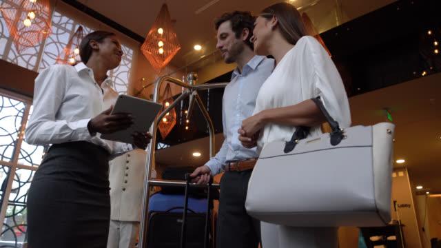 dost resepsiyonist yardım misafirler tablet bir anket doldurun ve sonra onlar orada el bagaj belboy için - hotel reception stok videoları ve detay görüntü çekimi