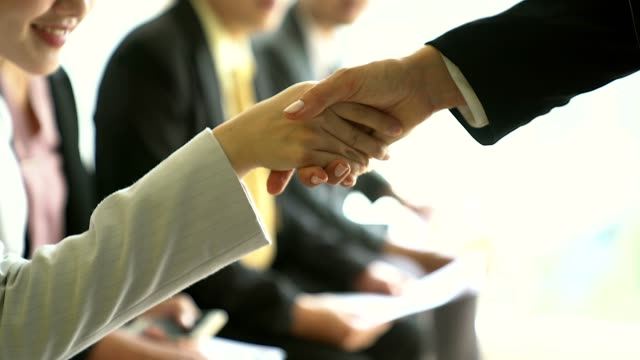 Friendly recruiters shaking hands with applicant just arrived for interview, diverse hr managers greeting candidate, nice to meet you and good first impression.