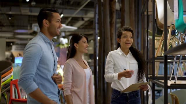 周りを示し家具店でカップルを助けるクリップボードを保持しているフレンドリーな販売の女性 - 小売販売員点の映像素材/bロール