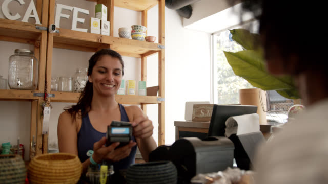 vänlig säljare på ett kafé charing cross kund för en kaffe medan hon betalar med ett kreditkort - frilansarbete bildbanksvideor och videomaterial från bakom kulisserna