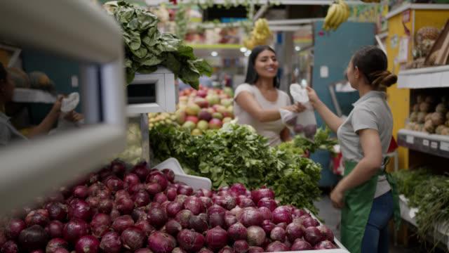 dost satıcı müşteri birkaç ile plastik bir torba teslim soğan seçmenize yardımcı - pazarcı stok videoları ve detay görüntü çekimi