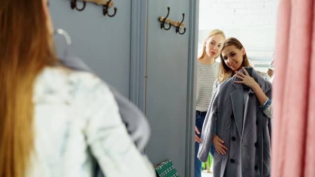Friendly saleswoman is helping female customer to choose a coat. Cheerful shopper is standing in fitting room in front of large mirror and fitting garment. Friendly saleswoman is helping female customer to choose a coat. Cheerful shopper is standing in fitting room in front of large mirror and fitting garment while chatting with shop assistant. saleswoman stock videos & royalty-free footage