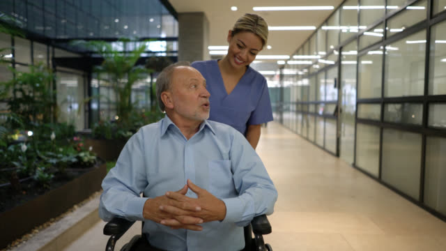 Friendly senior patient on wheelchair talking to beautiful nurse at the hospital Friendly senior patient on wheelchair talking to beautiful nurse at the hospital - healthcare concepts pushing wheelchair stock videos & royalty-free footage