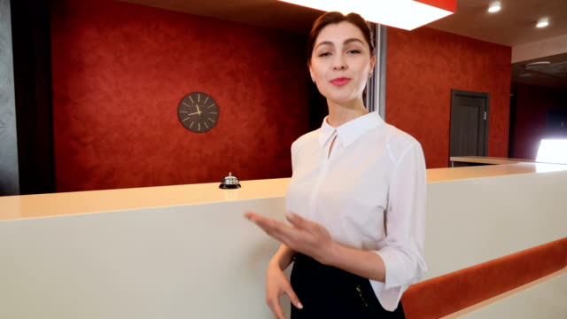 Friendly smiling hotel receptionist greeting hotel guest. video