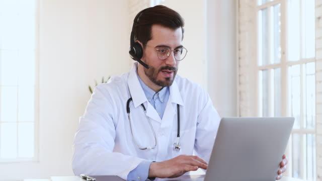 vänlig leende professionell manlig läkare bära headset rekommenderar telemedicin - videor med medicinsk undersökning bildbanksvideor och videomaterial från bakom kulisserna
