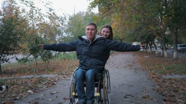 フレンドリーなサポート、幸せな障害者は秋の公園で笑顔の女性の車椅子に乗って楽しみを持っています - 車椅子スポーツ点の映像素材/bロール