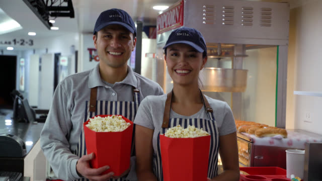 Friendly team of sales people at the cinema concession stand smiling at camera