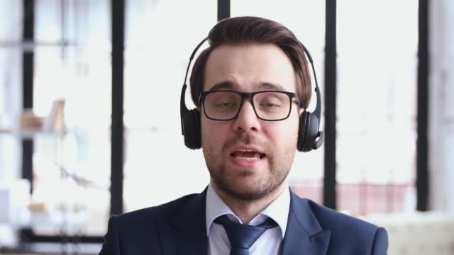 przyjazny operator telemarketera noszący zestaw słuchawkowy mówiący do kamery internetowej - słuchawki filmów i materiałów b-roll